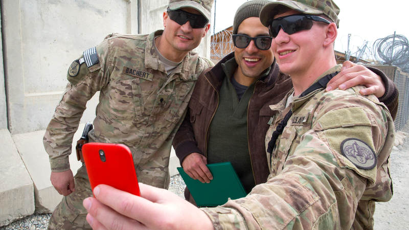 Actor Adam Rodriguez poses for a selfie with two service members during a USO tour stop in Afghanistan.