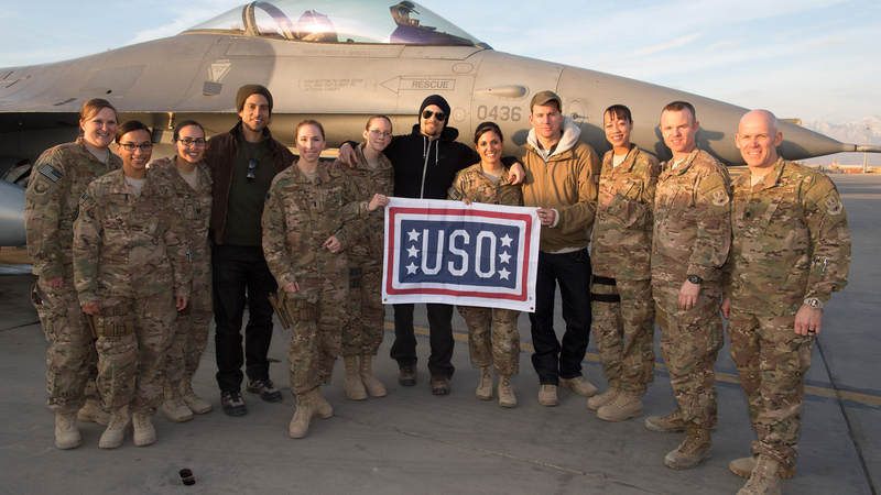 Actors Adam Rodriguez, Nick Zano and Channing Tatum pose with service members in front of an F-16 in Afghanistan.