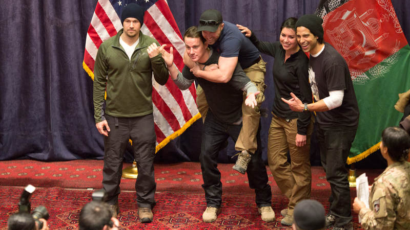 Channing Tatum gives a service member a piggy-back ride while posing for a photo during a USO tour.
