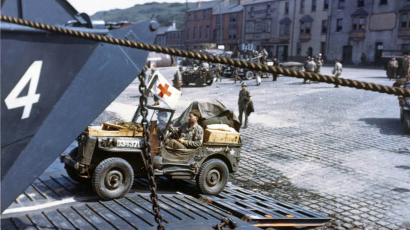 Jeeps drive onto an LCT at a port in Britain in preparation for D-Day.