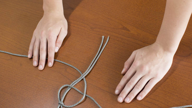 6. Take the left long strand of cord and cross it over the other long strand of cord and under the middle two short strands of cord.