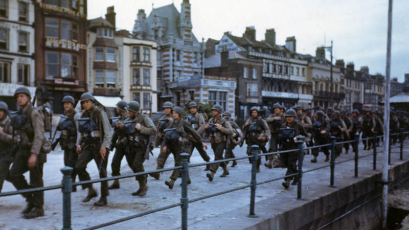 American troops march through the streets of a British port town on their way to the docks, where they will be loaded into landing craft for D-Day.