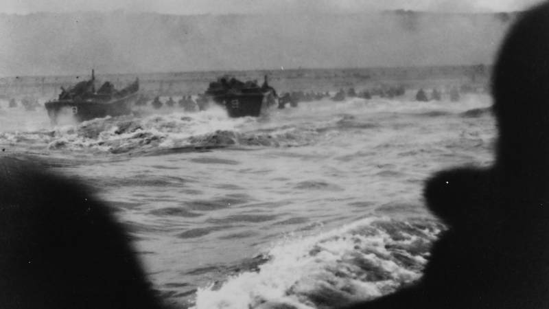 Coast Guard landing barges hit the French coast with the first wave of American troops under heavy fire from Nazi beach nests. This photo, taken from a landing barge by a Coast Guard combat photographer, shows the troops waist deep as they wade ashore. These landing barges shuttled back and forth from their assault transports to the beach carrying troops throughout D-Day.