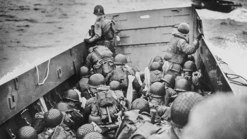 Helmeted American soldiers crouch, tightly packed, behind the bulwarks of a Coast Guard landing barge in the historic sweep across the English Channel to the shores of Normandy. Minutes later, they dashed up the beach under fire from the Nazi defenders. These Coast Guard barges rode back and forth through D-Day bringing wave upon wave of reinforcements to the beachhead.