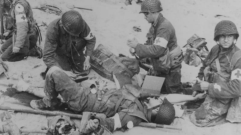 American medics render first aid to troops in the initial landing on Utah Beach. In the background, other members of the landing parties dig into the soft sand of the beach.