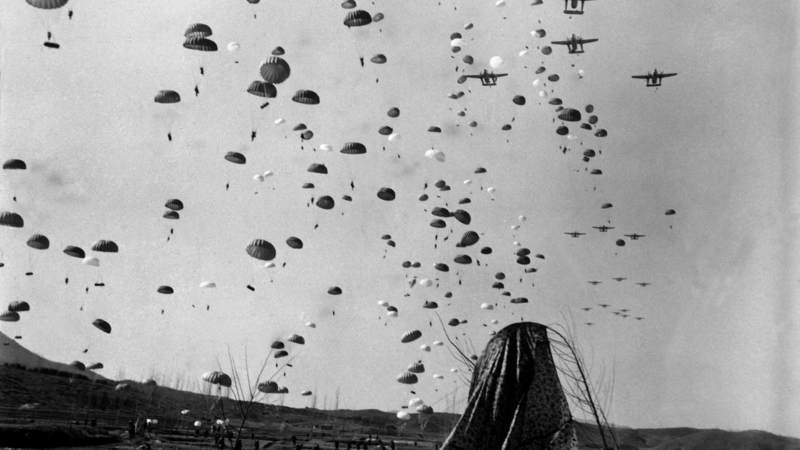 Paratroopers float earthward from C-119s to cut off retreating enemy units south of Munsan, Korea on March 23, 1951.