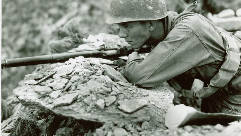 An American soldier scans the area in front of his observation post on the front line somewhere in Korea.