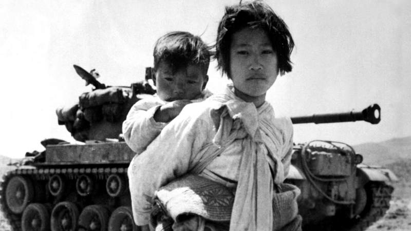 A Korean girl with her brother on her back moves wearily past a stalled tank near Haengju, in Kyonggi Province, Korea, June 9, 1951. The war, which claimed millions of lives and left the Korean peninsula devastated, halted with the signing of an armistice on July 27, 1953.