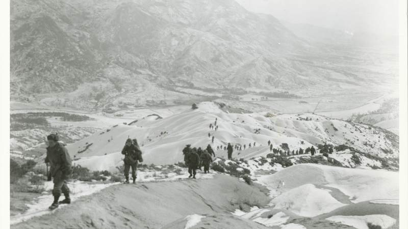 Soldiers from the 19th Infantry Regiment march in the rough Korean terrain in 1951.