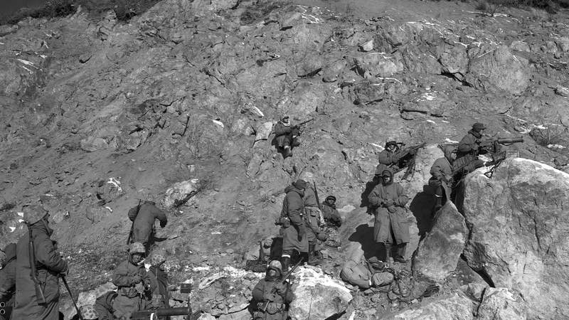 First Marine Division infantrymen take to a rugged hillside in wiping out enemy troops who have set up a roadblock against the Allied advance.
