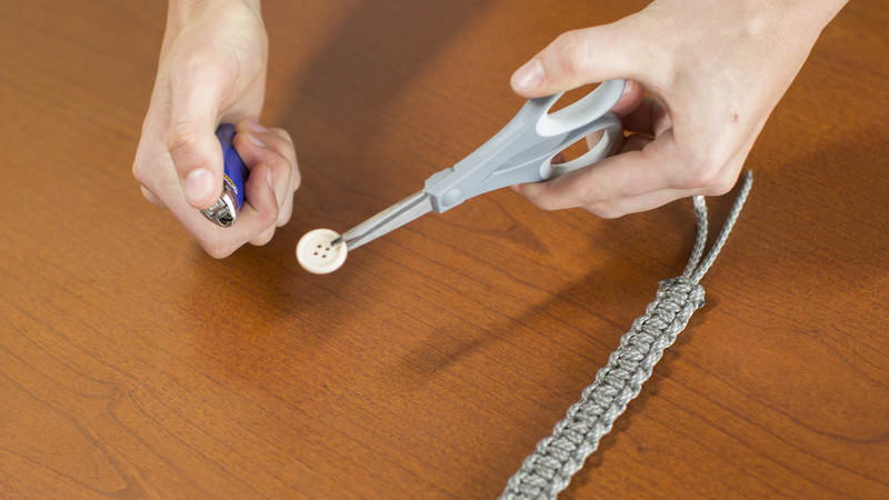 13. Holding the edge of the button with the ends of your scissors, melt the center of the button for 2-3 seconds. Immediately after melting, use a pen to poke a hole through the button. You might have to repeat this process a couple of times.