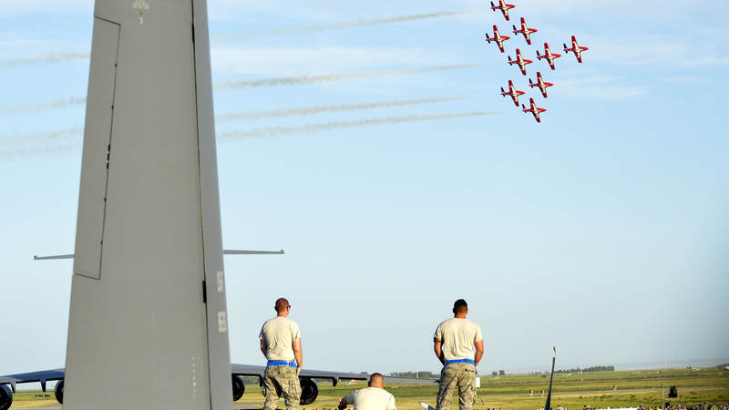 U.S. airmen watch the Royal Canadian Forces Snowbirds perform in Lethbridge, Alberta, Canada.