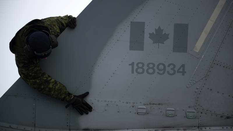 A member of the Royal Canadian Air Force completes a post flight check during an exercise on Thule Air Base, Greenland.