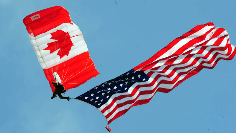 A member of the Canadian SkyHawks parachutes with the American flag.