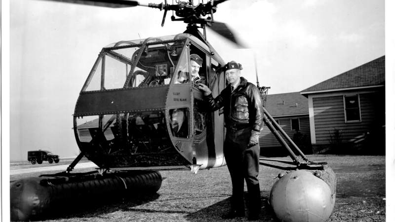 Commander Frank Erickson, the Coast Guard's first helicopter pilot, poses with a Hoverfly helicopter around 1943.
