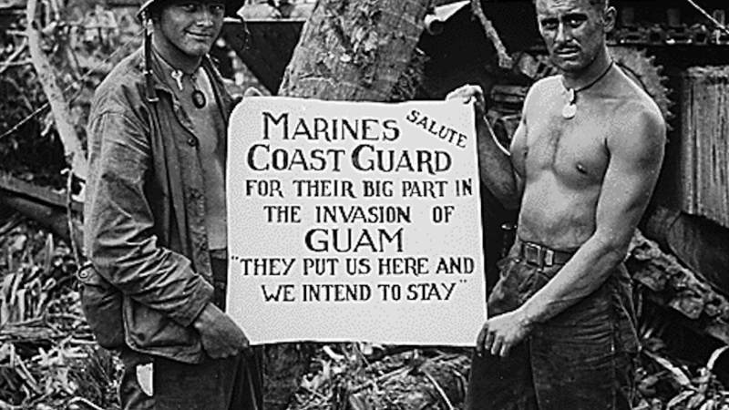 Marines William A. McCoy and Ralph L. Plunkett hold a sign saluting Coast Guard forces in 1944 after the Japanese were defeated at Guam.