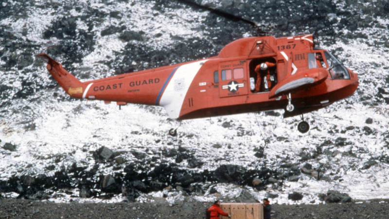 An HH-52A Pelican helicopter from the  Coast Guard icebreaker Northwind airlifts a crated musk ox to its new habitat during a joint Denmark-U.S. relocation operation in 1986.