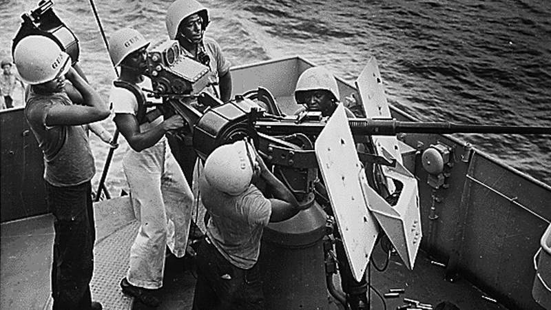 Five steward's mates stand at their battle stations as a gun crew aboard a Coast Guard-manned frigate in the southwest Pacific in 1944.