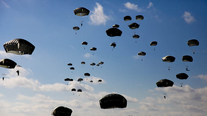 Army paratroopers with the 82nd Airborne jump out of an Air Force C-130.