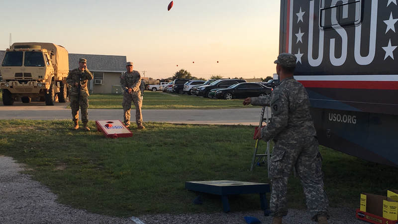 Service members play games outside the USO Mobile unit.