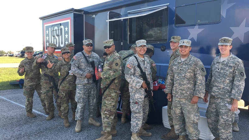 Service members smile outside the USO Mobile unit at Fort Swift, the staging location for much of the military's Harvey relief efforts.
