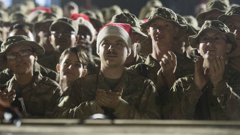 Soldiers from the 3rd and 4th Brigade, 10th Mountain Division, watch the USO Holiday Tour at Q-West, Iraq, on Christmas Day.