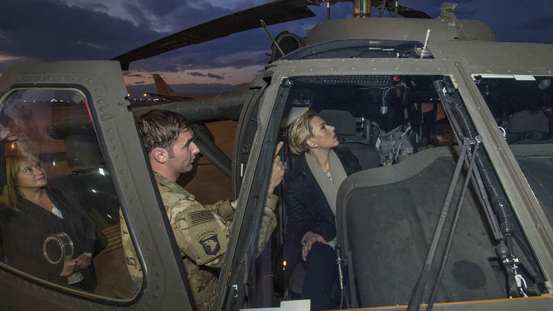 A pilot explains the controls of a Blackhawk helicopter to Scarlett Johansson during the trip to Incirlik Air Base, Turkey.