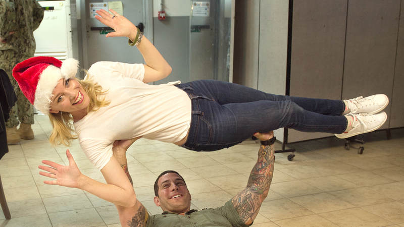 A service member bench presses Elizabeth Banks during her 2015 trip to Camp Lemonnier in Djibouti.