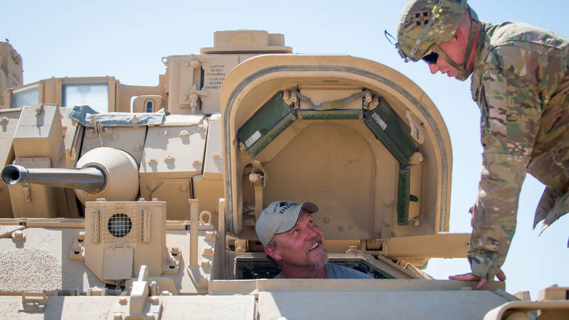 Adkins checks out the inside of a tank at Camp Buehring, Kuwait, during a USO tour to the Middle East.