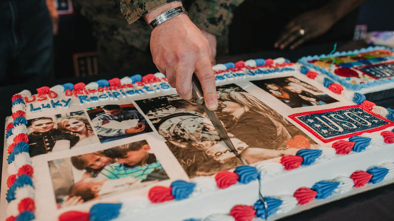 Marine Staff Sgt. Dustin Johnson cuts the ceremonial first slice of his extra-special birthday cake. USO photo by Amber Craig.