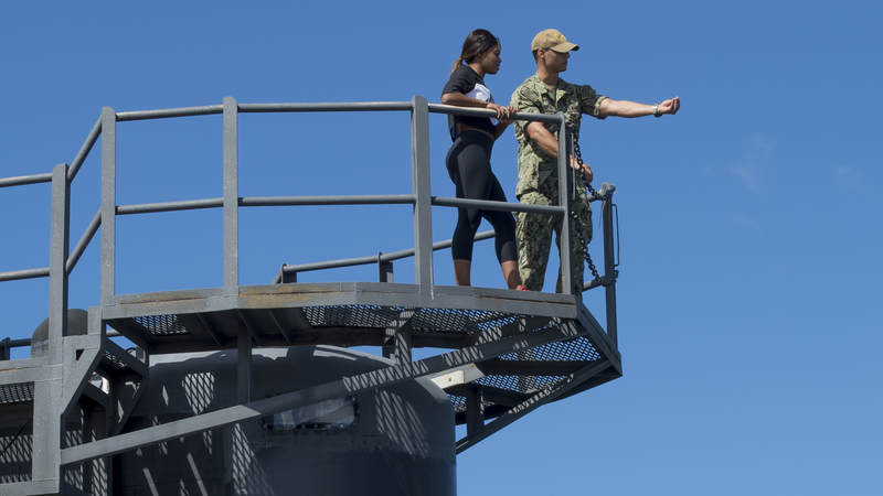 Navy Lt. j.g. Caleb Mazzola shows Gabby Douglas the Vertical Launch Systems (VLS) from the sail of the Asheville.