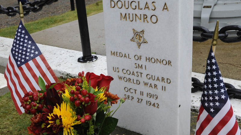 Signalman 1st Class Douglas Munro's grave marker is surrounded by challenge coins, saint pendants, rate and rank insignia, and other items that have been left by military members and veterans in Cle Elum, Wash.