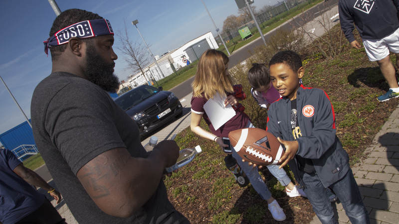 Carolina Panthers defensive end Mario Addison signs and autograph for a young fan in Germany during the 2018 USO-NFL tour.