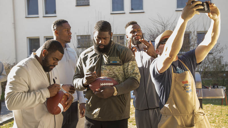 From left to right, NFL players Mark Ingram, Carlos Dunlap, Mario Addison and Latavius Murray sign autographs and take photos during the 2018 USO-NFL tour of military bases in Italy and Germany.