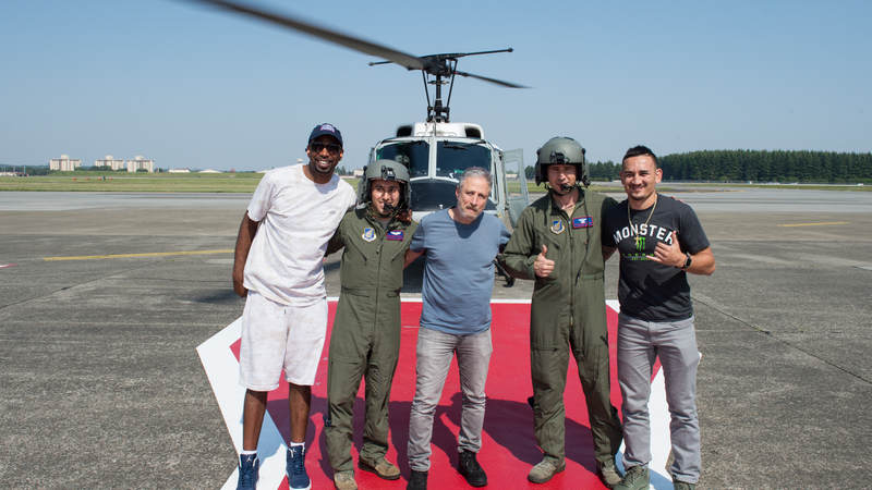 "NBA legend Richard ""Rip"" Hamilton, comedian Jon Stewart and UFC fighter Max ""Blessed"" Holloway pose for a photo with a UH-1 Huey helicopter aircrew after a helicopter tour of Tokyo from Yokota Air Base, Japan. Army photo by Sgt. James McCann"