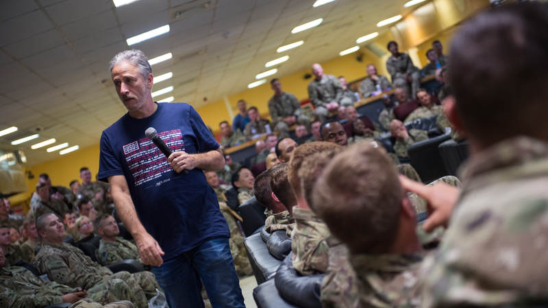 "Former ""Daily Show"" host Jon Stewart performs for troops during the USO Spring Tour in April. Army photo by Sgt. James McCann"