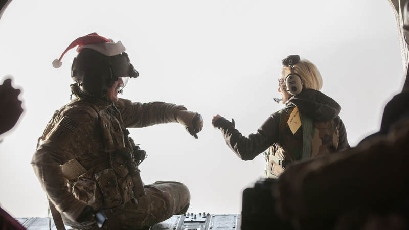 Pickler fist bumps a service member while taking a flight over Afghanistan to another USO tour stop at Forward Operating Base Walton.
