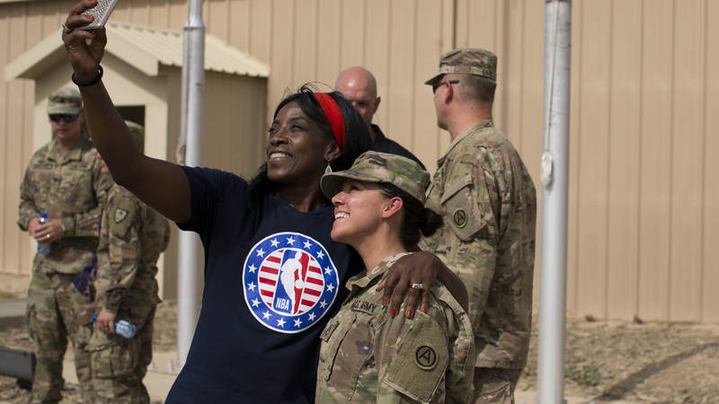 Ruthie Bolton takes a selfie with a service member.