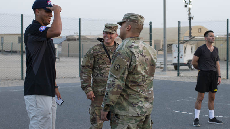 Kevin Martin smiles while talking with service members.