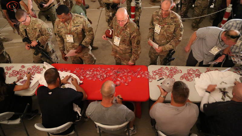 Falcons players, coaches and cheerleaders sign autographs at a USO-hosted event at Erbil Air Base.