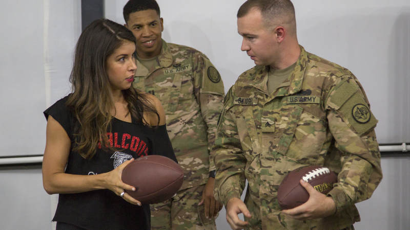 Falcons cheerleader Alexandria Giannini chats with a service member during a meet-and-greet session during the tour.