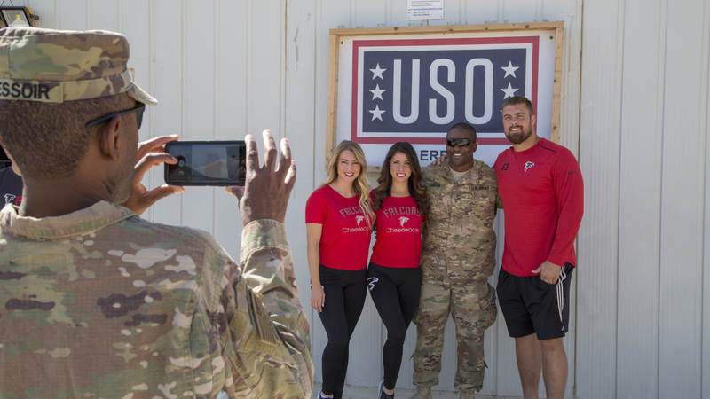 Falcons cheerleaders Brianna Stade, left, Alexandria Giannini and offensive lineman Ben Garland pose for a photo outside USO Erbil in Iraq.