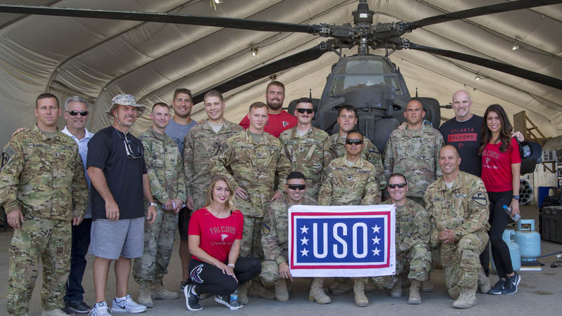 The Falcons crew poses with troops in front of an AH-64 Apache helicopter at Erbil Air Base, Iraq, during a USO tour.