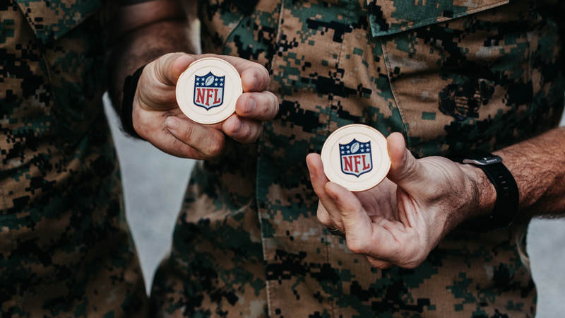 Marines show off some NFL challenge coins during the USO-NFL Legends tour to Okinawa, Japan, on July 25-26. USO photos by Amber Craig