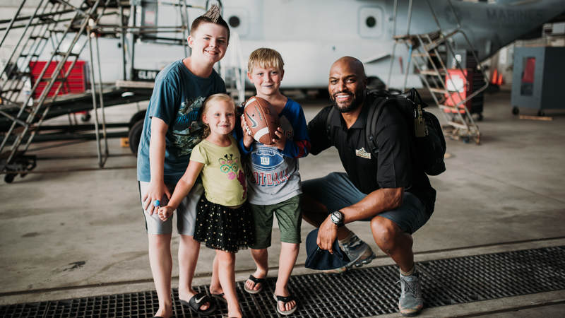 Former New York Giants star Amani Toomer spends time with some young NFL fans during the USO-NFL Legends tour to Okinawa, Japan, on July 25-26. USO photos by Amber Craig