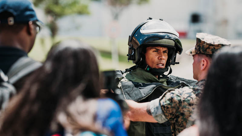 Former Kansas City Chiefs and San Diego Chargers linebacker Donnie Edwards tries on military gear during the USO-NFL Legends tour to Okinawa, Japan, on July 25-26. USO photos by Amber Craig