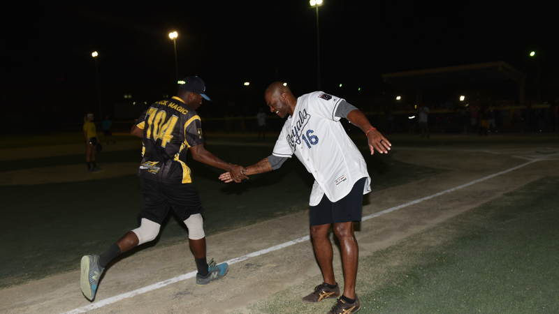 Former right fielder for the Kansas City Royals, Reggie Sanders, high-fives a service member during a pickup game of softball in Kuwait. USO Photo by Neal Preston.