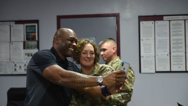 Reggie Sanders takes a photo with a fan while on a USO Tour with Kansas City Royals greats in Kuwait. USO Photo by Neal Preston.