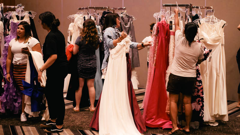Military spouses and service members peruse ball gowns at USO Okinawa's Operation That's My Dress event, where dresses are free-of-charge. USO Photo by Ashley Perez.