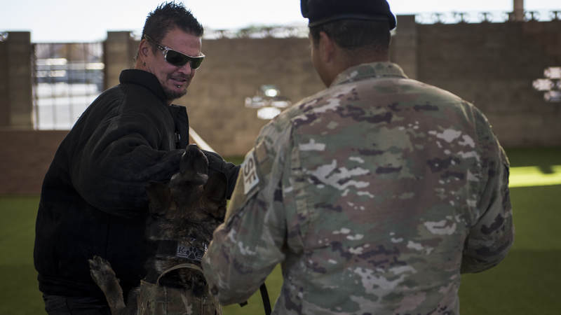 Dan Donegan, guitarist for the band Disturbed, receives a bite from a military working dog during a demonstration at Nellis Air Force Base, Nevada, October 24.